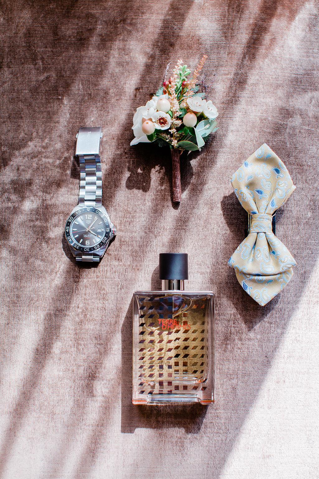 μια μπουτονιέρα, ένα παπιγιόν, το ρολόι και το άρωμα του γαμπρού, the groom's accessories for the wedding