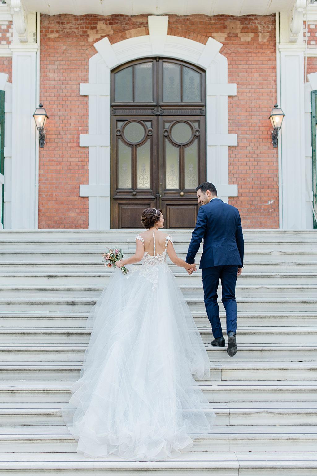 Το ζευγάρι ανεβαίνει τα σκαλιά κατά την φωτογράφιση τους, bride and groom during photoshoot in wedding in thessaloniki