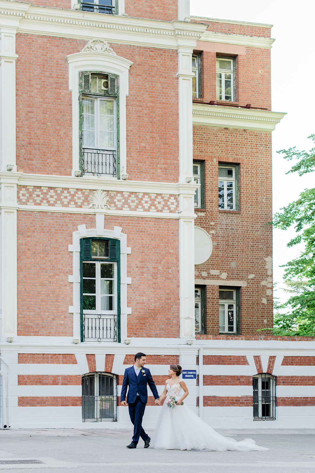 The groom and the bride walk in front of a neoclassical building in Thessaloniki