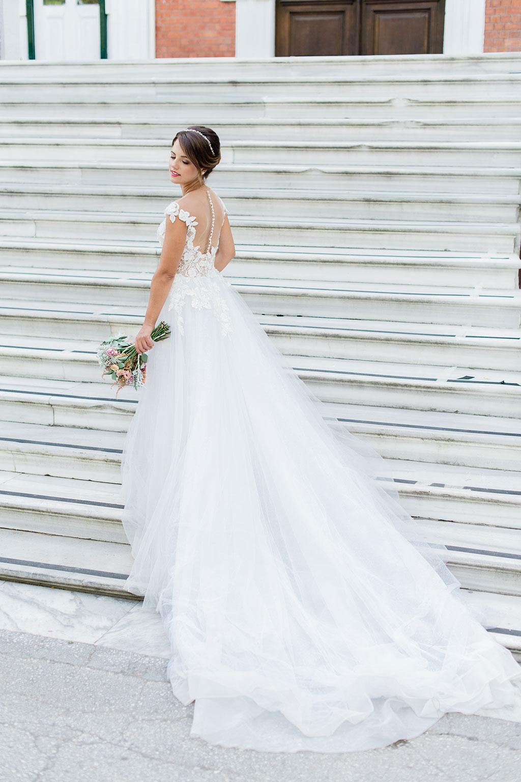 νύφη που κρατάει την ανθοδέσμη της και ποζάρει με το υπέροχο νυφικό της. a bride with her long bridal dress during photoshoot