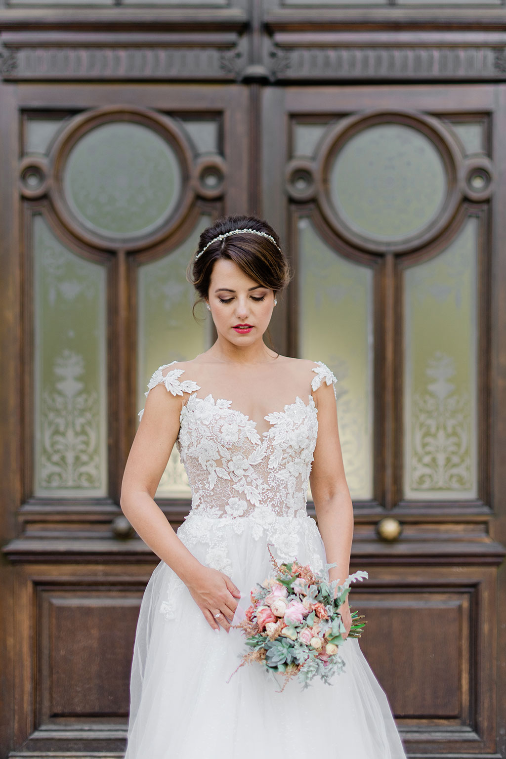 υπέροχο νυφικό πορτραίτο, a bride posing with her wedding bouquet in front of a door