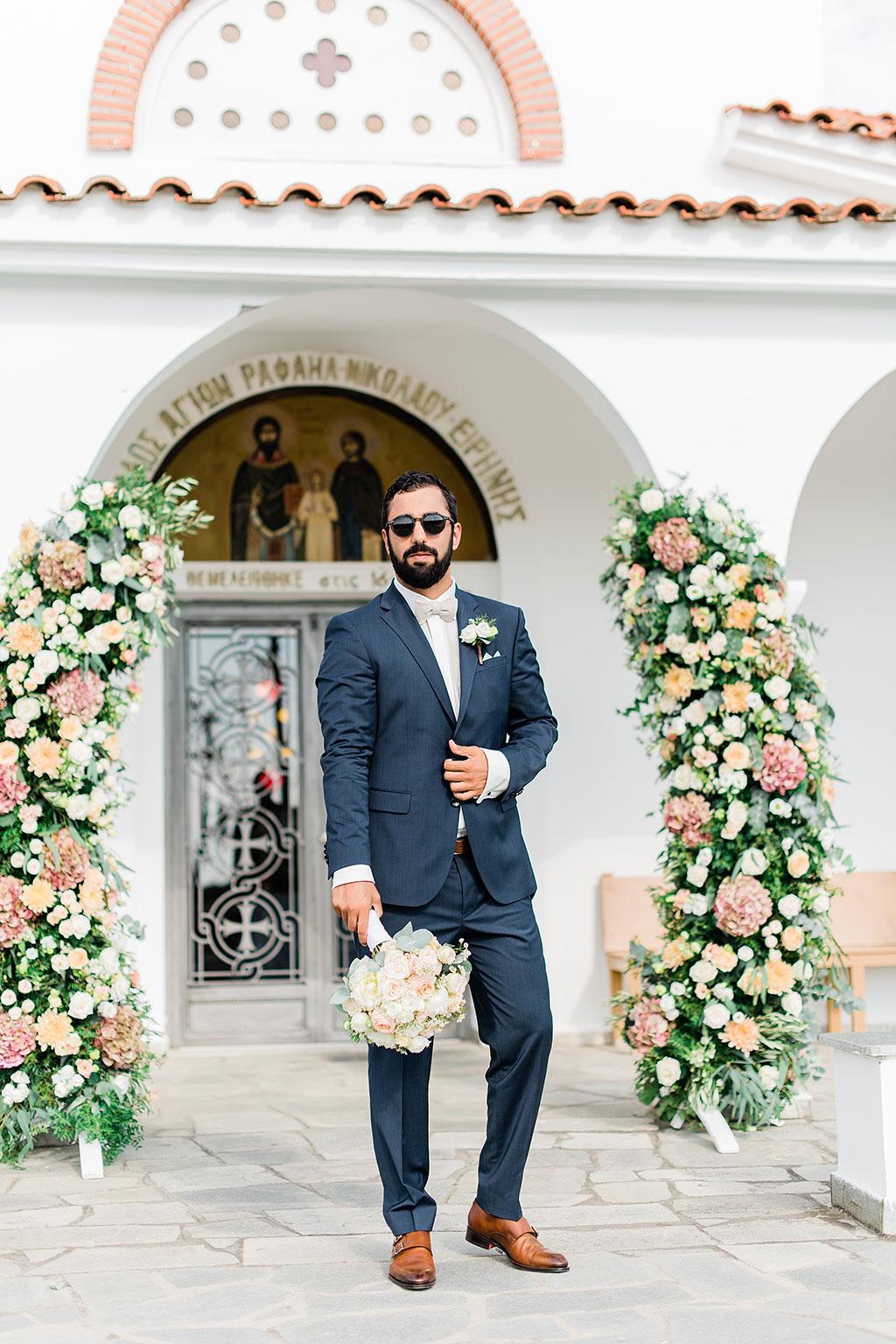 ο γαμπρός περιμένει την νύφη στην εκκλησια με το νυφικό μπουκέτο στο χέρι