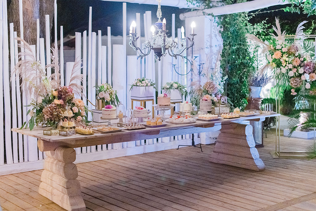 the candy bar, table with sweets and cakes in a wedding